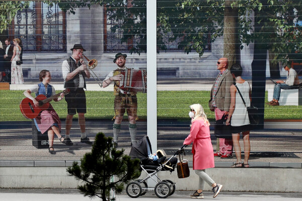 A woman in Munich passing a mural showing traditional Bavarian musicians. Europe's economy has been reviving from the pandemic.