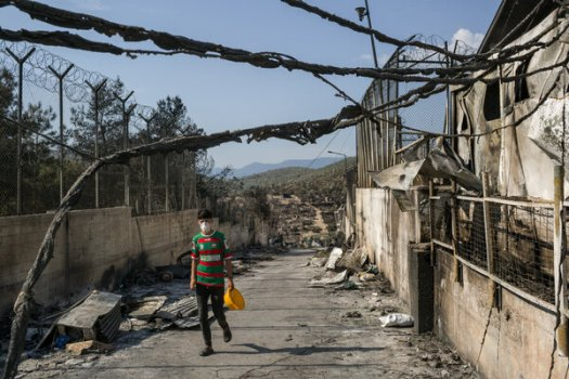 A displaced refugee from Afghanistan walks through the destroyed compound of the Moria camp in Lesbos, Greece in September.