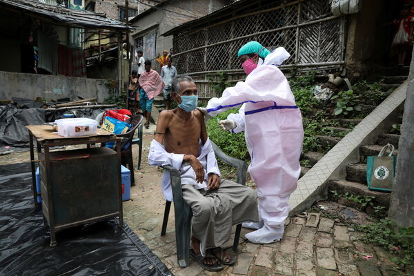 Receiving a Covid shot during a door-to-door vaccination and testing drive in West Bengal State, India, on Monday.