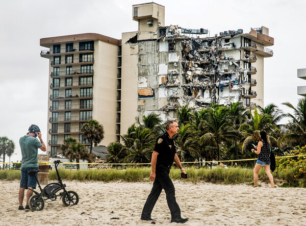 Onlookers observe the aftermath of a collapsed condominium building in Surfside, Fla., a city just north of Miami Beach, Fla., on Thursday, June 24.