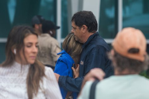 A couple embracing in a community center on Friday where people waited for information on missing people believed to have been caught in the collapse of the Champlain Towers South building in Surfside, Fla.