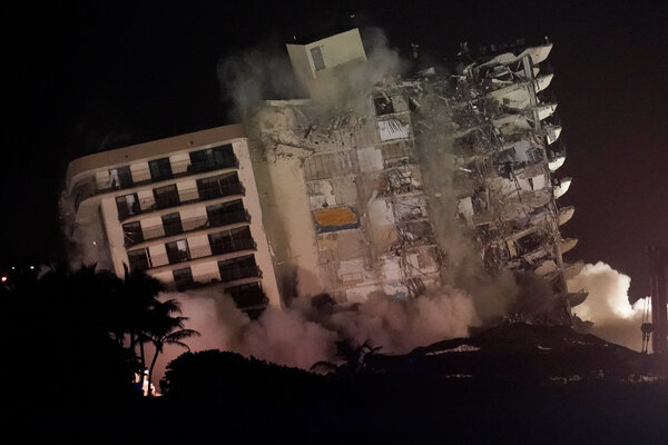 The damaged remaining structure at the Champlain Towers South condo building collapses in a controlled demolition, Sunday, July 4, 2021, in Surfside, Fla.