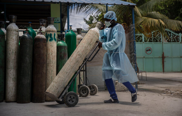 A hospital employee transporting oxygen tanks in Port-au-Prince, Haiti, in June.