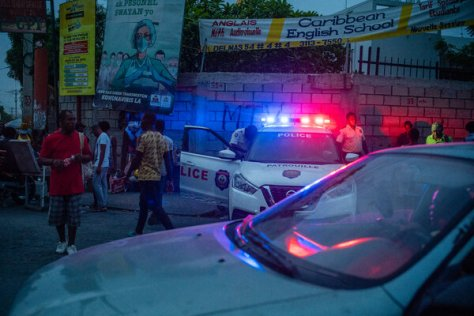 A police checkpoint in Port-au-Prince, Haiti, a country in turmoil after its president was assassinated. A sign above encourages efforts to stop the coronavirus.