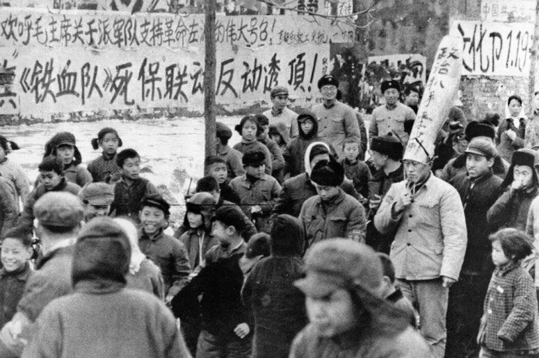 1967年,在北京的一場批鬥會上,紅衛兵牽著一名戴高帽的國家幹部遊街。