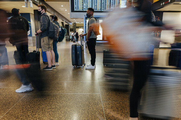 Travelers wait in a bag drop line in the ticketing area at Seattle-Tacoma International Airport in May.
