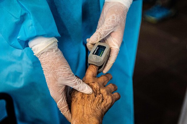 A health worker checks oxygen levels of an elderly person before giving her a dose of the Pfizer-BioNTech vaccine.