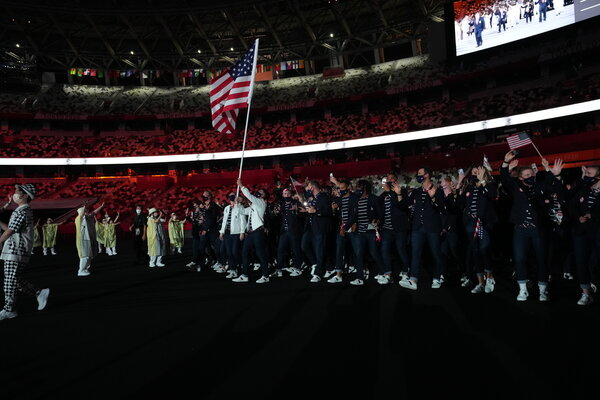 Sue Bird, wearing a white coat on the left, was a flag-bearer for the United States during the opening ceremony. The other was the baseball player Eddy Alvarez, standing next to Bird carrying the flag.