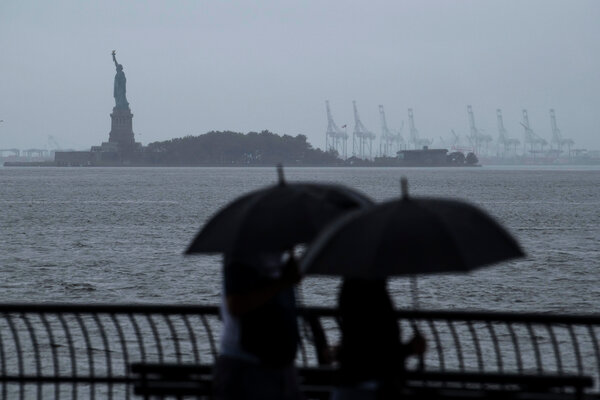 People carried umbrellas in lower Manhattan on Sunday morning as the city prepared for Tropical Storm Henri.