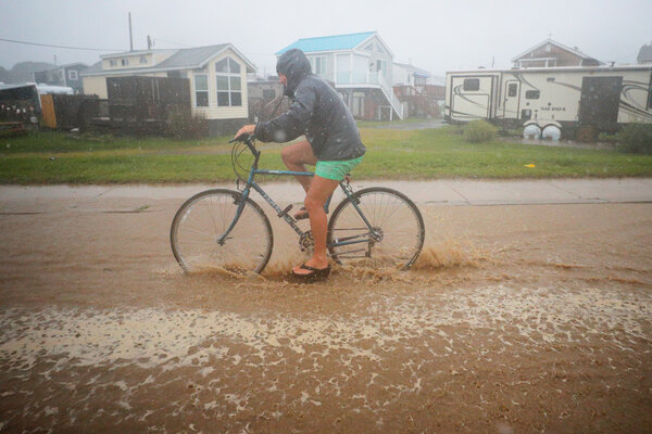 A cyclist rode through a flooded street as Tropical Storm Henri approached South Kingston, R.I., on Sunday.