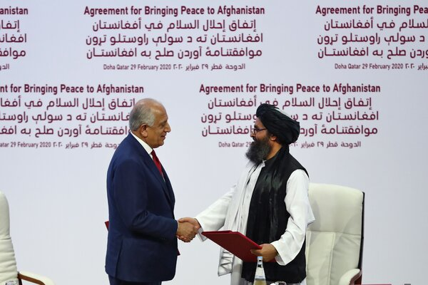 The U.S. special representative for Afghanistan reconciliation, Zalmay Khalilzad, and the Taliban co-founder Mullah Abdul Ghani Baradar shaking hands after signing a peace agreement in Qatar in February 2020.
