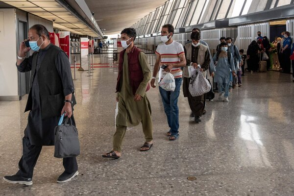 Refugees from Afghanistan walked to a bus on Monday after being processed at Dulles International Airport outside Washington.