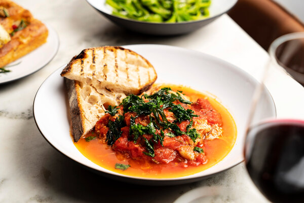 Chicken is braised with tomatoes and peppers, then pulled apart and reintroduced to the pan juices.