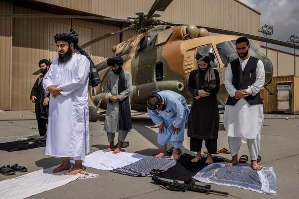 Talibs saying their afternoon prayers before an MI17 helicopter damaged by departing US forces at the HKIA airport in Kabul, Afghanistan, yesterday.