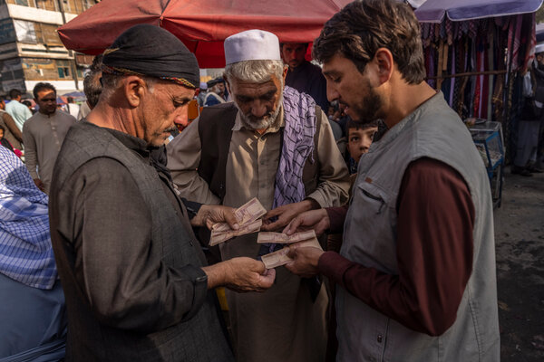 Money changers working with customers at their stalls in Kabul in August. Halawa, the informal banking network, is crucial to many Afghans.