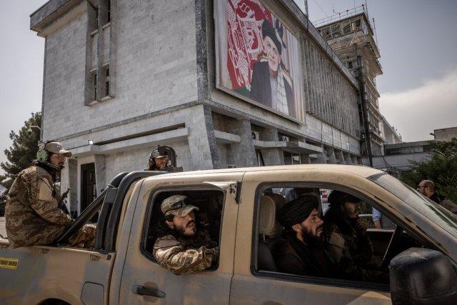 周四,塔利班武装分子在喀布尔机场驶过前总统阿什拉夫·加尼的宣传画。