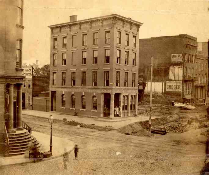 View of business on the corner of a street in Williamsburg, Brooklyn, with men in the doorway and on the street in the foreground. Construction is taking place on the street and on the adjacent lot. ca. 1867.