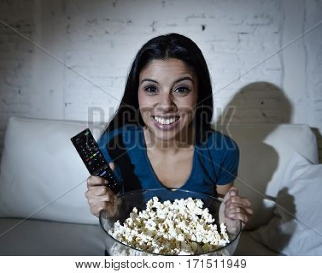 Young Beautiful Spanish Woman Home Alone Watching Television Smiling Sitting At Sofa Couch On Living Room