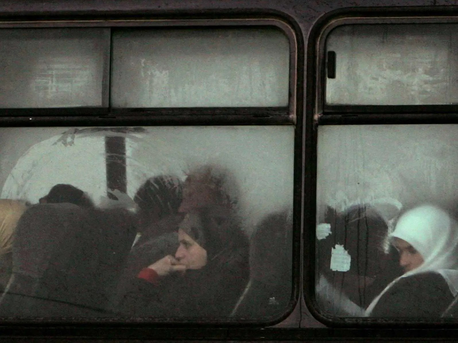 Palestinian women sit on bus at West Bank crossing