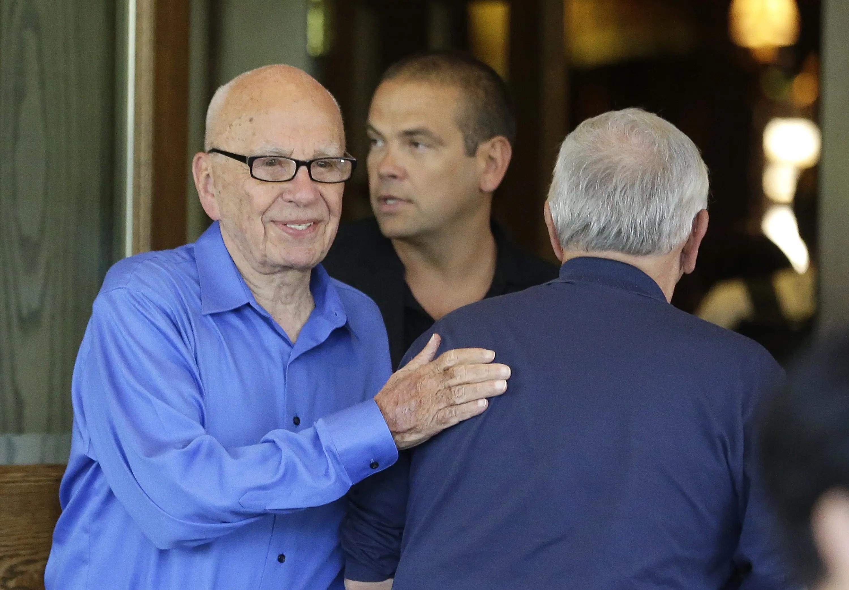 Rupert Murdoch pats NBA commission David Stern on the back.