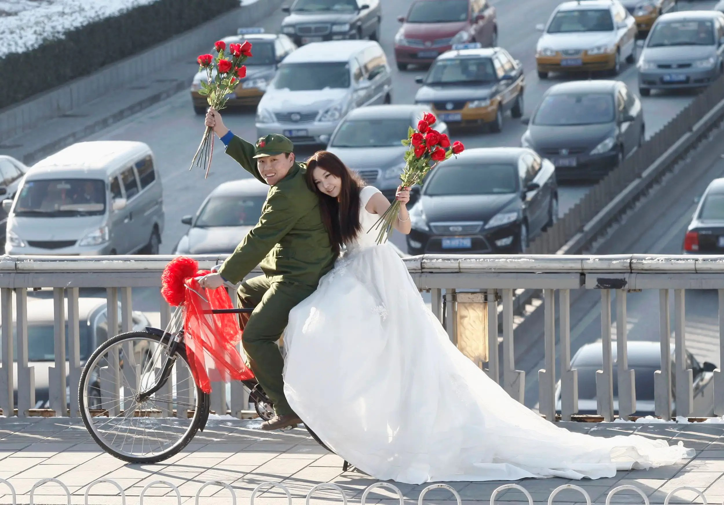 An engaged couple poses on a pedestrian bridge on Valentine's Day in central Beijing.