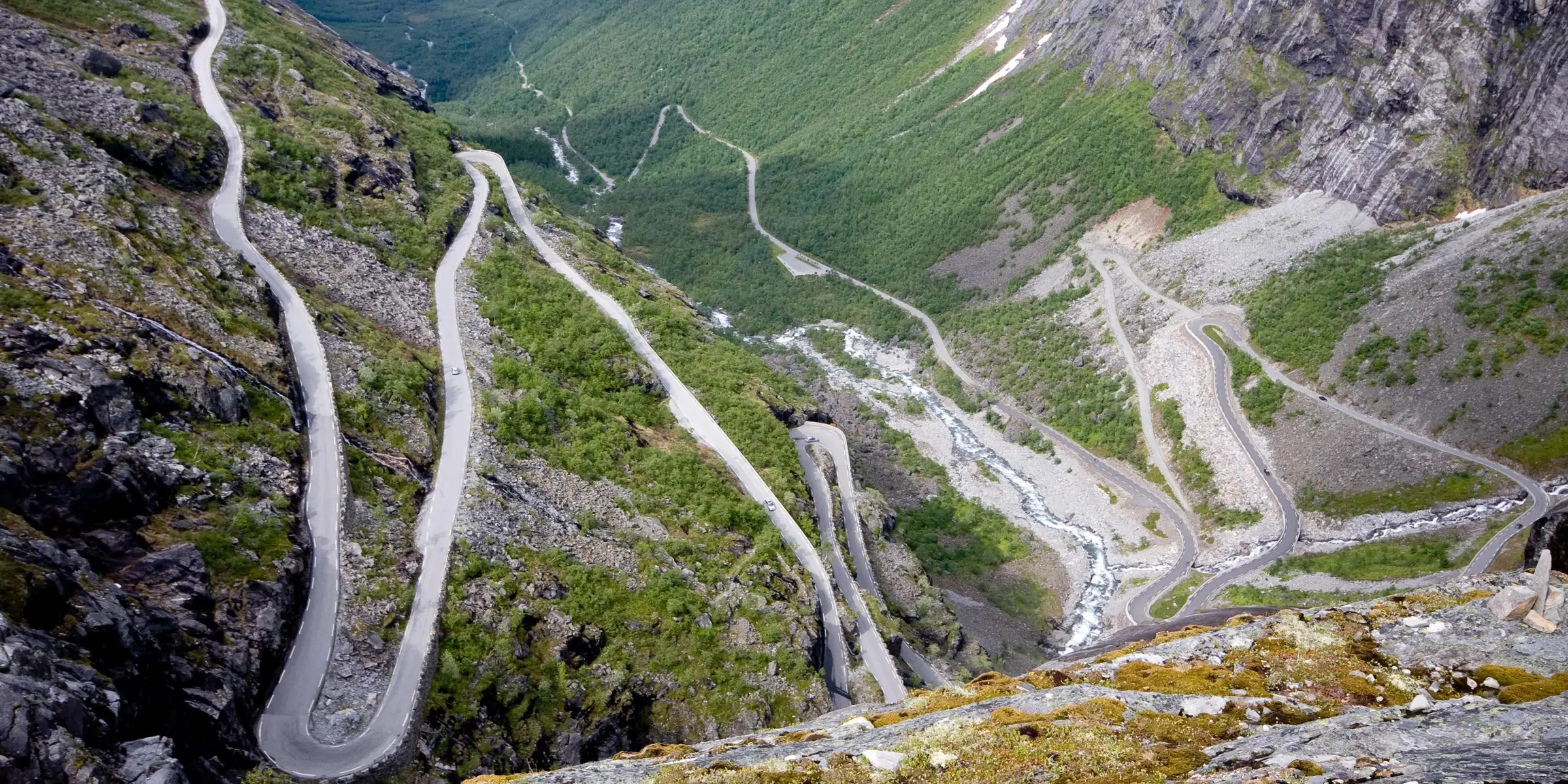 """The Trollstigen road in Norway means """"troll ladder,"""" and that name is very fitting for this extremely narrow and steep winding road. If you make it to the top, you'll be rewarded with views of the Stigfossen waterfall, a 1,050-foot waterfall that tumbles over the mountains."""