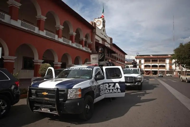 Police stand guard outside the town hall after a shooting between federal forces and armed civilians in the town of Apatzingan, Michoacan January 6, 2015.  REUTERS/Alan Ortega