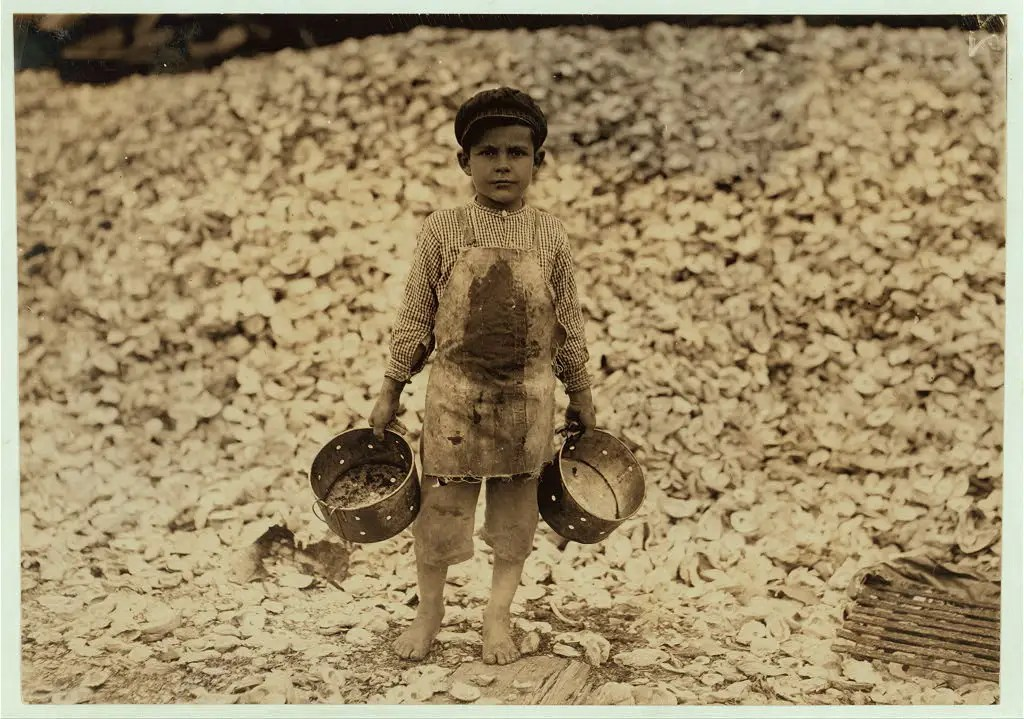 Manuel, the young shrimp-picker, 5 years old and a mountain of child-labor oyster shells behind him. He worked the year before. Understands not a word of English. Dunbar, Lopez, Dukate Company. Location: Biloxi, Mississippi, February 1911.