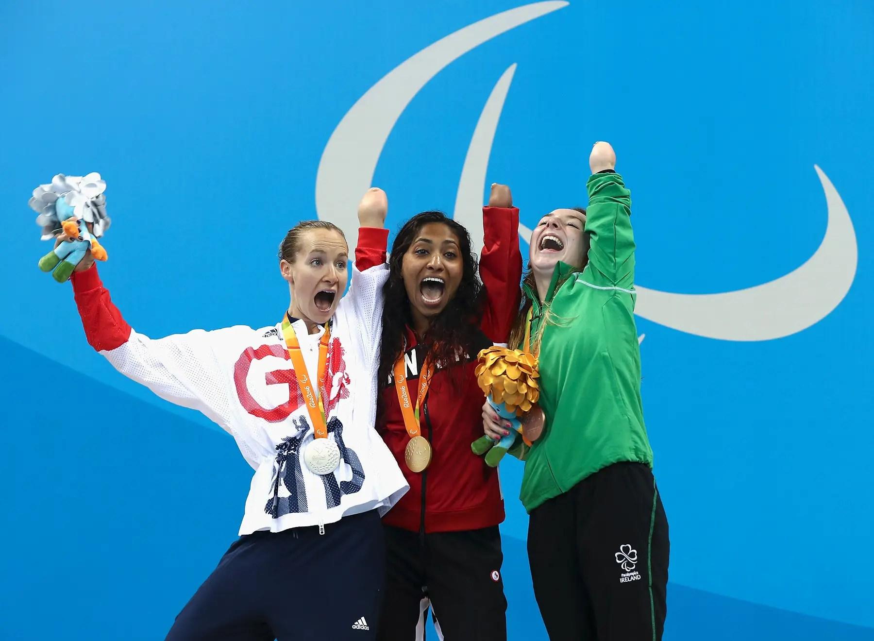 La medallista de plata Claire Cashmore de Gran Bretaña, medalla de oro Katarina Roxon de Canadá y medallista de bronce Ellen Keane de Irlanda celebran en el podio en la ceremonia de medalla para los 100 metros braza Mujeres