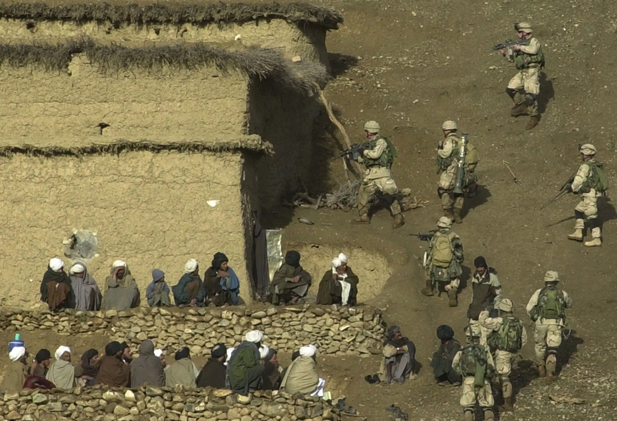 "Afghan villagers watch as US soldiers from the 82nd airborne's Bravo Company search a house for suspected Taliban and al-Qaida forces in the central part of the Baghran river valley during the finishing stages of ""Operation Viper"" in Helmand Province, southern Afghanistan on Monday, February 24, 2003."