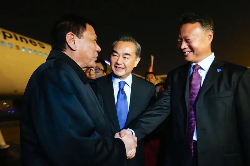President of the Philippines Rodrigo Duterte (L) shakes hands with Chinese ambassador to the Philippines Zhao Jianhua (R), as Chinese Foreign Minister Wang Yi (C) looks on, at airport in Beijing, China, October 18, 2016. CNS Photo via REUTERS