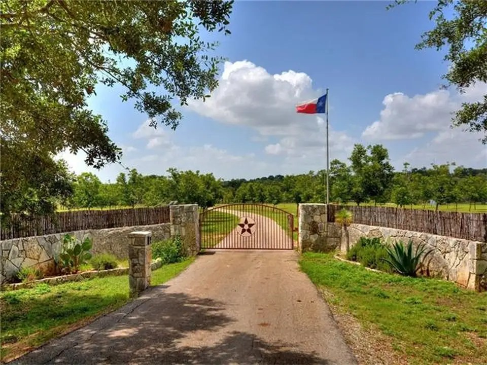 A large gate and Texas state flag marks the entrance.