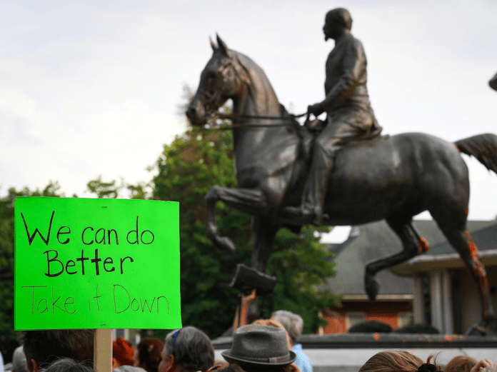 Protesters gather below a monument dedicated to Confederate Major John B. Castleman while demanding that it be removed from the public square in Louisville, Ky., US, August 14, 2017. Confederate statues meant to be everlasting symbols of white supremacy Confederate statues meant to be everlasting symbols of white supremacy rts1bt8b