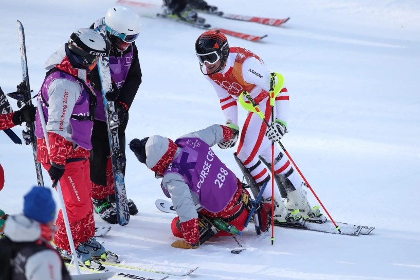 Matthias Mayer assists a course marshall after a skiing crash