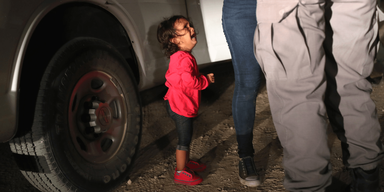A two-year-old Honduran asylum seeker cries as her mother is searched and detained near the U.S.-Mexico border on June 12, 2018 in McAllen, Texas.