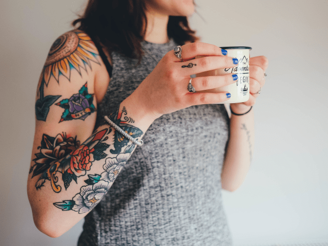 woman with tattoos drinking coffee
