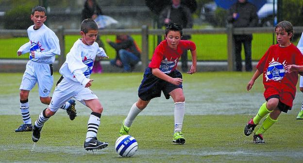 Dos equipos de fútbol formativo disputan el esférico durante un partido. / USOZ