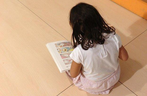 Una niña lee un libro en una biblioteca infantil.