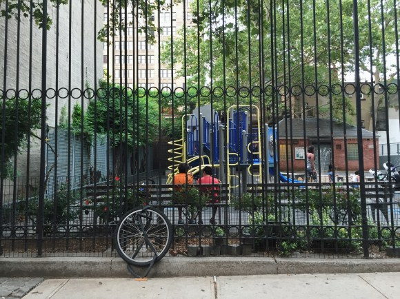 Two kidschat on a bench at a park on the upper West side, flanked by a single/locked up bike wheel