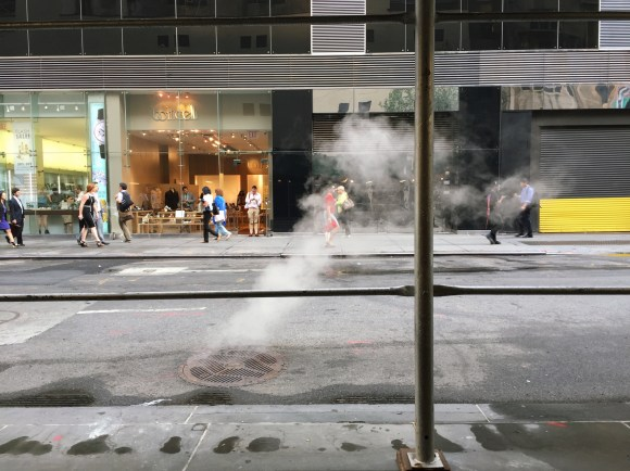 A woman in a red dress walks across the street in the midst of street smoke.