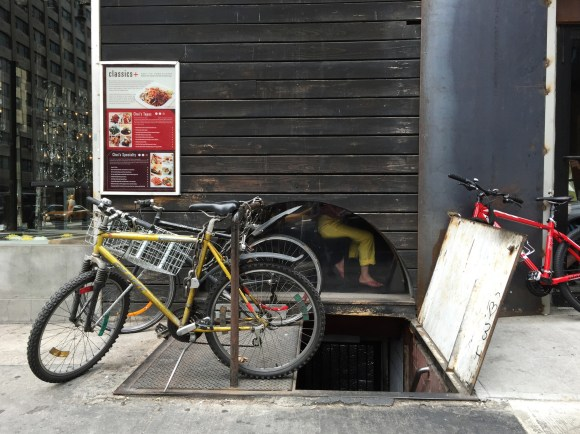 A woman dines at an asian restaurant in yellow pants, matching the yellow delivery bike just outside.
