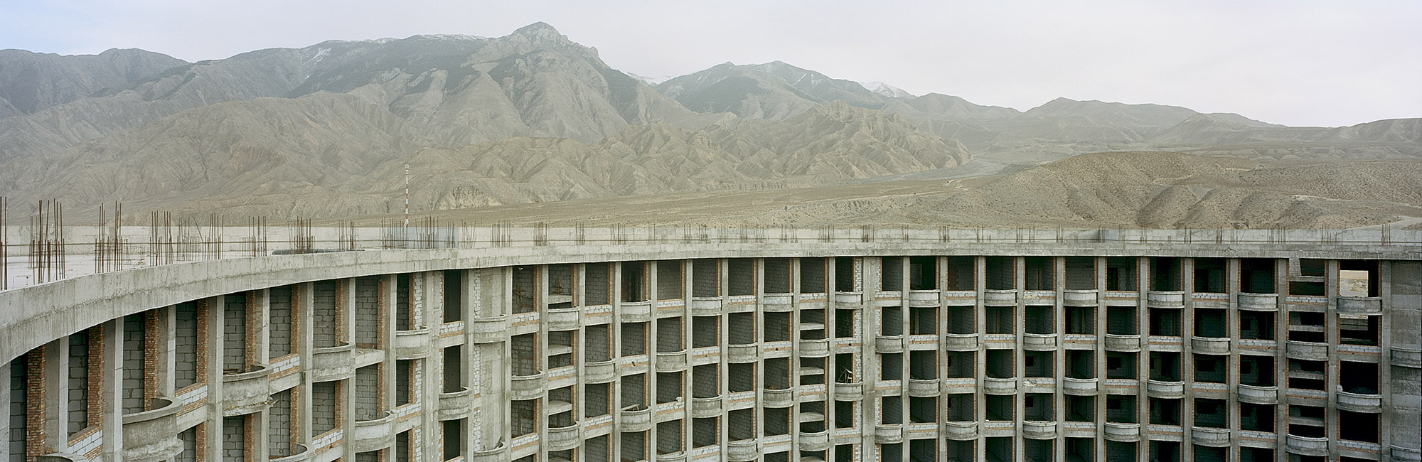 "Abandoned 5 Star Hotel Construction.  Guide, Qinghai, China. 2014   One of the benefits of creating the Sanjiangyuan National Nature Reserve, according to China's State Council, would be ""ecological protection and construction"" on the plateau. Development in the protected ecosystem of the Reserve, however, soon extended beyond tourism, to the mining of gold and other minerals, road construction, and real estate development. Meanwhile some of the tourism-related projects were lost to changing political winds: according to a local security guard, construction on this 5-star hotel came to a halt when developers couldn't secure the necessary permits after a turnover in local government personnel. While much new construction in the area has reached completion, scientists have raised concerns that large towns and cities, and the infrastructure that connects them create higher densities of humans that will inevitably increase the stress on the local ecology."