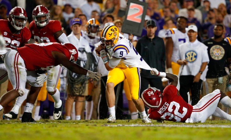 Alabama linebacker Dylan Moses (32) tries to tackle LSU quarterback Joe Burrow (9) by his jersey as defensive lineman Phidarian Mathis (48) closes in, during the second half of an NCAA college football game in Baton Rouge, La., Saturday, Nov. 3, 2018. Alabama won 29-0. (AP Photo/Gerald Herbert)