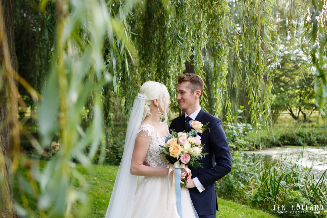 Bride and groom at leeds castle kent by willow trees