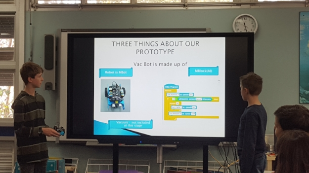 Students presenting their VacBot (vacuum robot) prototype at the MicroMakers II Hackathon Day.