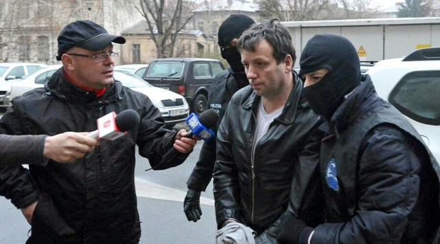 Marcel Lazar Lehel, aka Guccifer, is escorted by masked policemen in Bucharest after his arrest in 2014. © Silviu Matei / Reuters