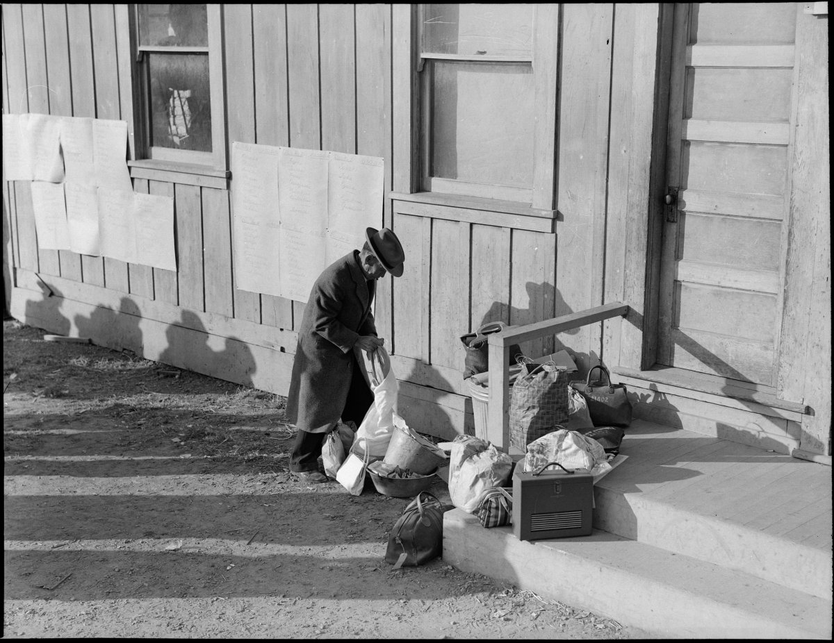 Centerville, California. This farmer rearranges his personal effects as he awaits evacuation bus. Evacuees of Japanese ancestry will be housed in War Relocation Authority centers for duration.