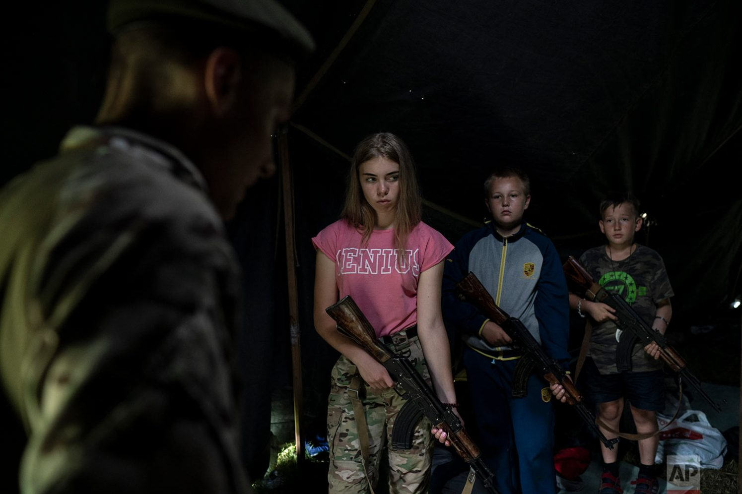"""Participants of the """"Temper of will"""" summer camp, organized by the nationalist Svoboda party, hold their AK-47 riffles as they receive instructions during a tactical exercise on July 28, 2018, in a village near Ternopil, Ukraine. Campers as young as 8 years old practice using assault rifles. They are taught to shoot to kill Russians and their sympathizers. (AP Photo/Felipe Dana)"""