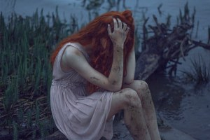 Girl crying beside a river
