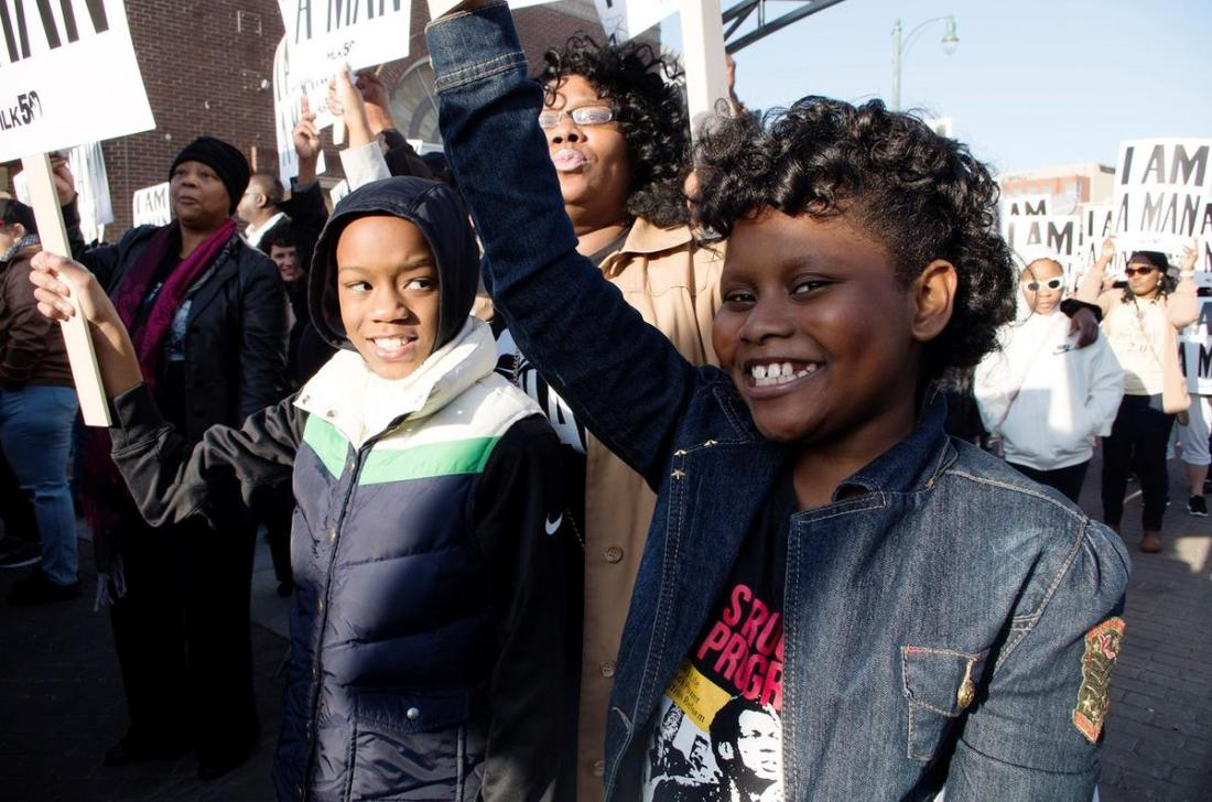 "Lashundra Richmond stands behind her son Phillip and her goddaughter Madison as they hold up ""I AM A MAN"" signs during the reenactment of the famous Withers photograph.  CREDIT PHOTO BY SYDNEY MATZKO"